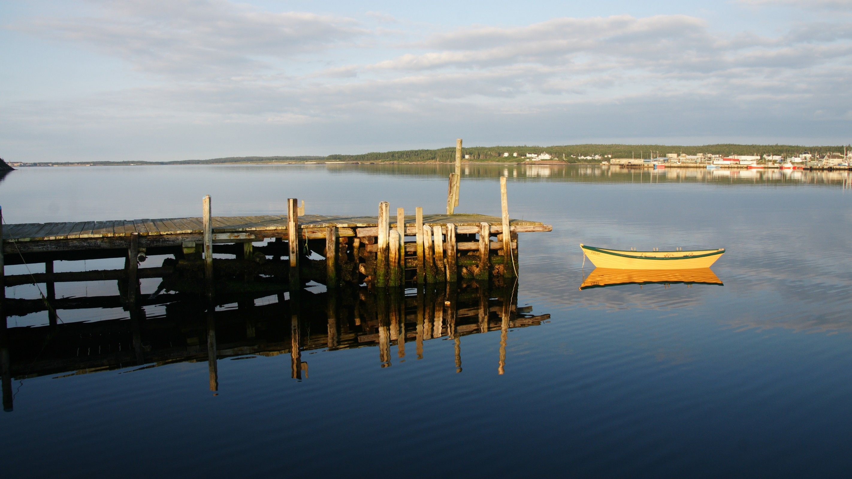 Yellow boat tied up to wooden wharf on calm harbour in Louisbourg, Nova Scotia, Cape Breton Island, Canada