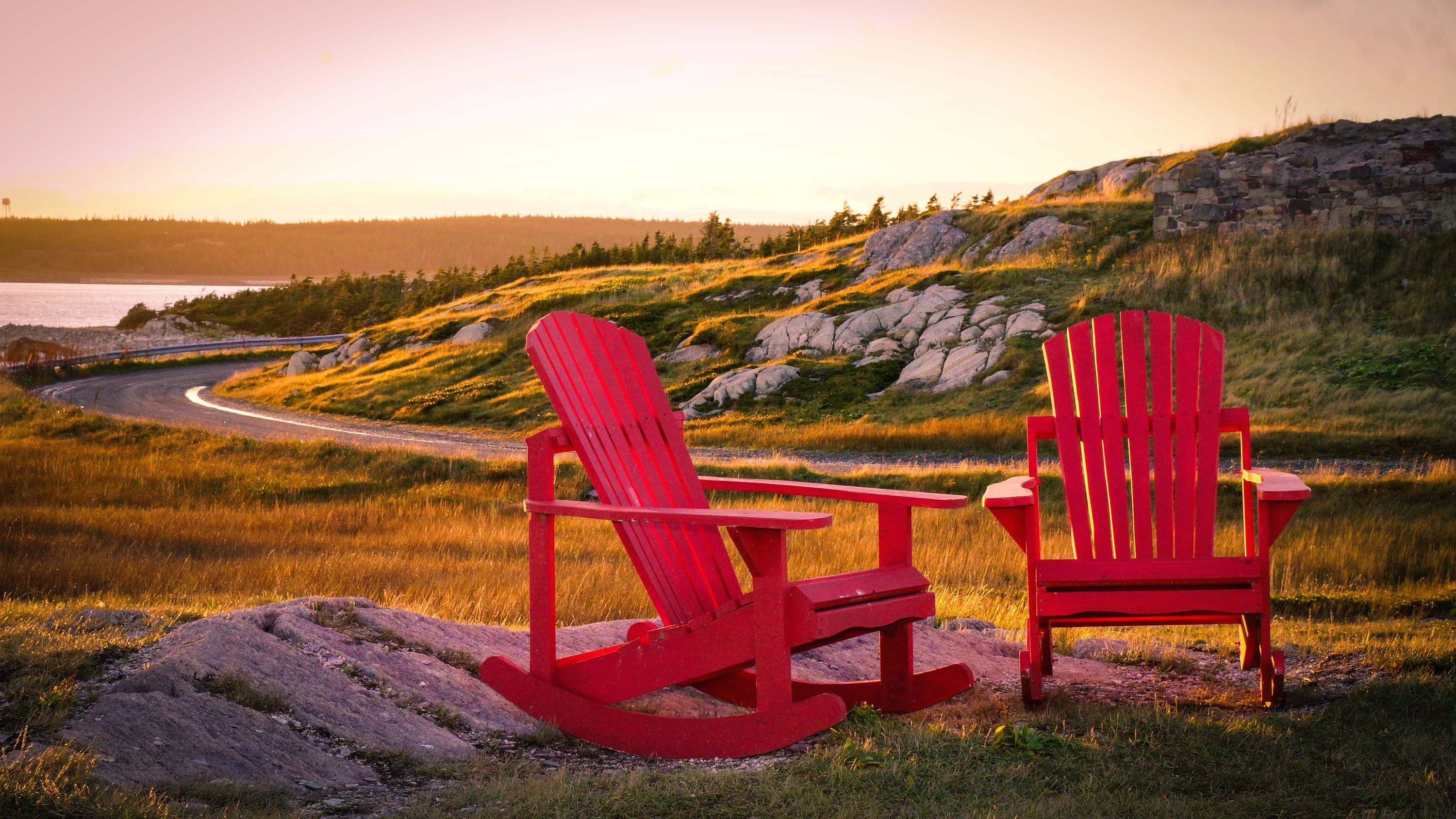 Two red lawn chairs on the coast in Louisbourg, Nova Scotia, Canada