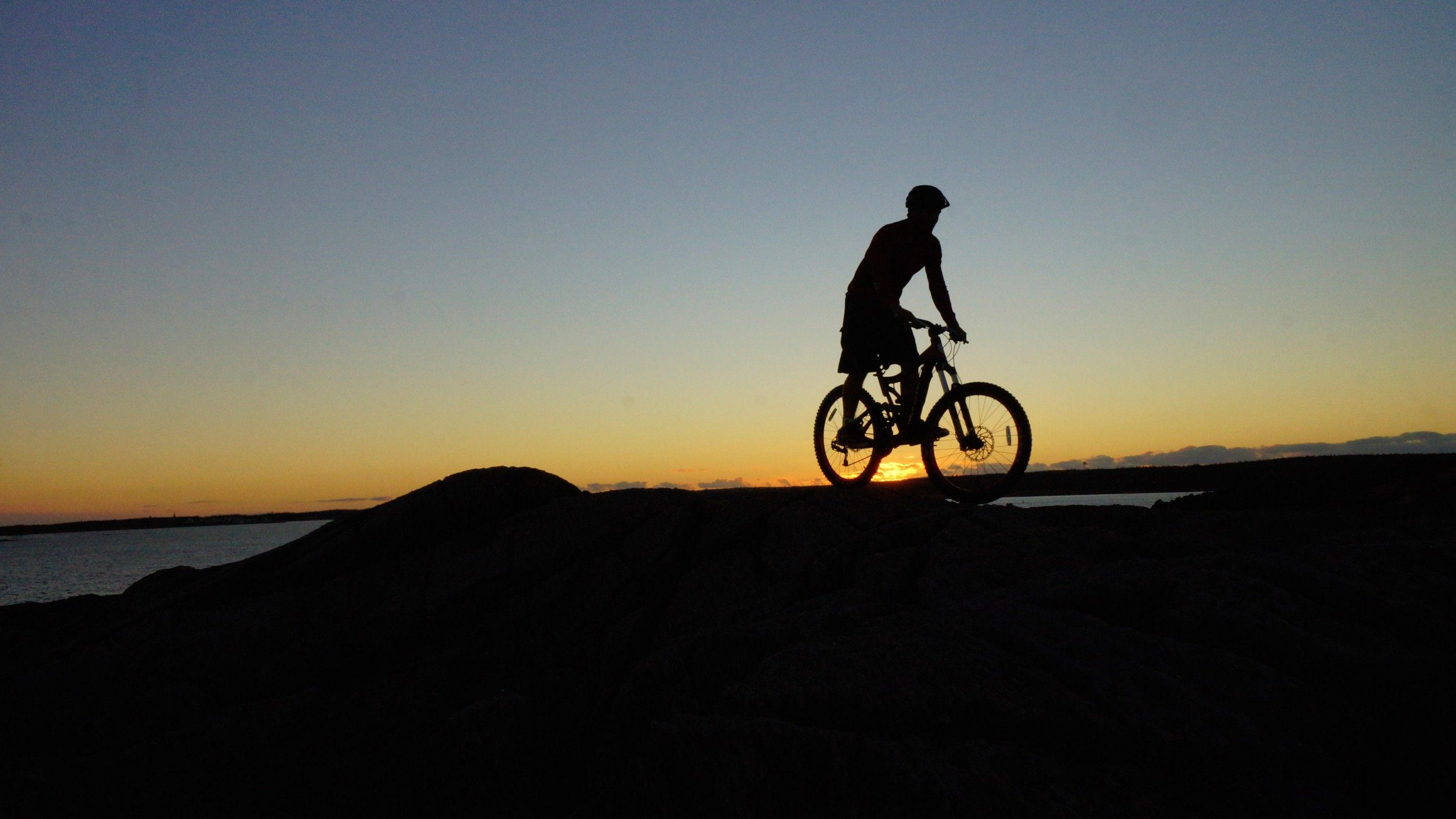 Mountain biker pedalling across rocks in Louisbourg, Cape Breton Island, Nova Scotia, Canada