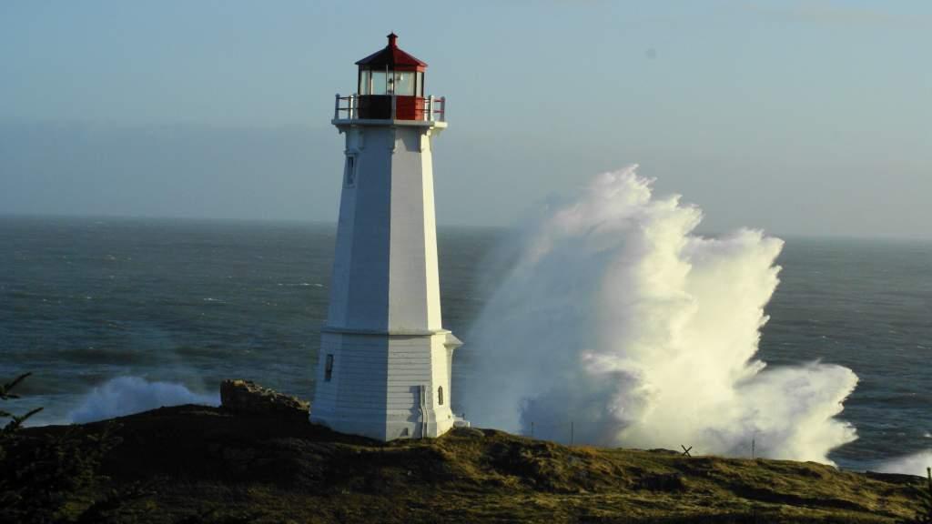 Waves breaking behind the Louisbourg Lighthouse on Cape Breton Island, Nova Scotia, Canada