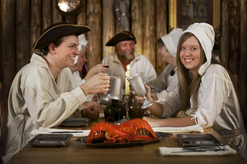 Tourists enjoying a lobster meal in period costume in Louisbourg, Nova Scotia.