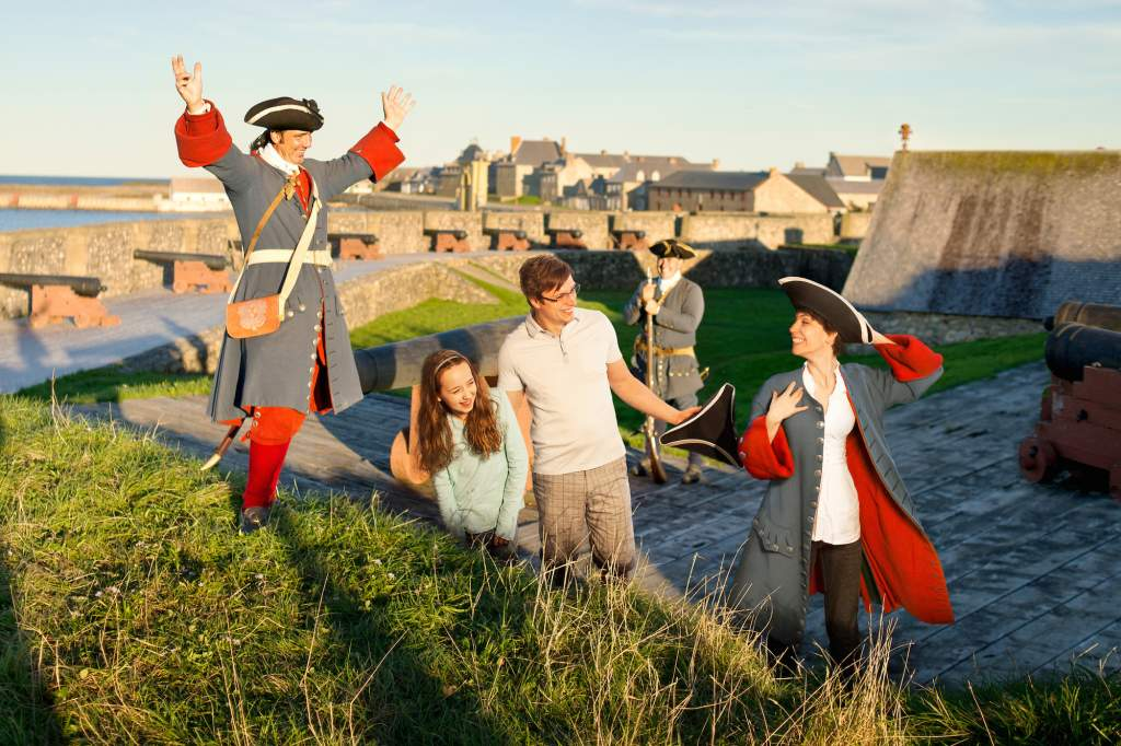 Couple interacting with historical reenactors at Fortress of Louisbourg Historical Site, Nova Scotia, Canada